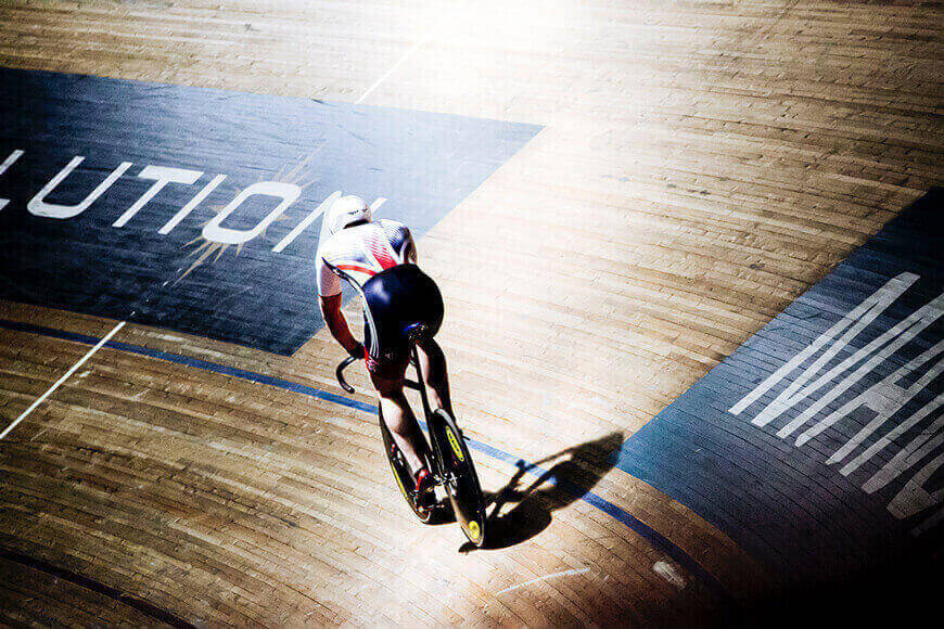 A competitive cyclist spins around an indoor track.