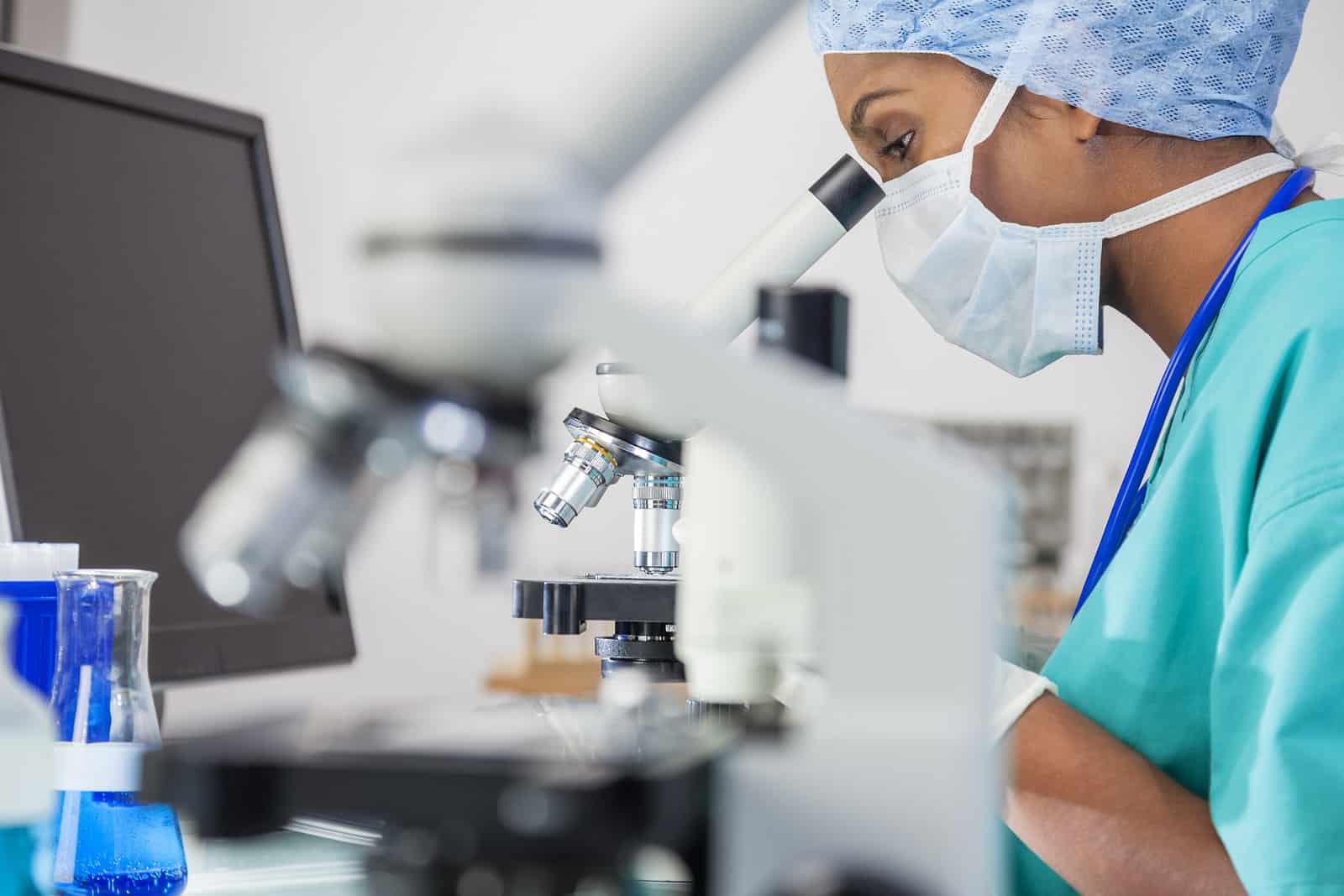 A Female Doctor Looks Through a Microscope