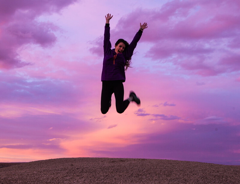 A Woman Energetically Jumps Up in The Air