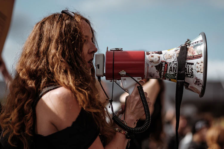 A female protestor speaks into a megaphone