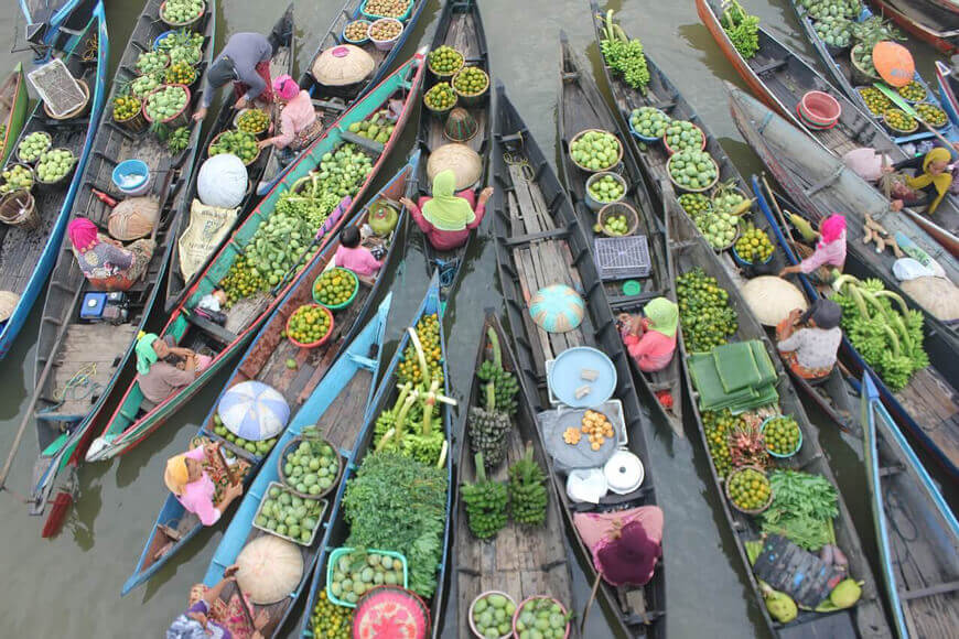 Longboats-floating-side-by-side,-filled-with-exotic-fruits