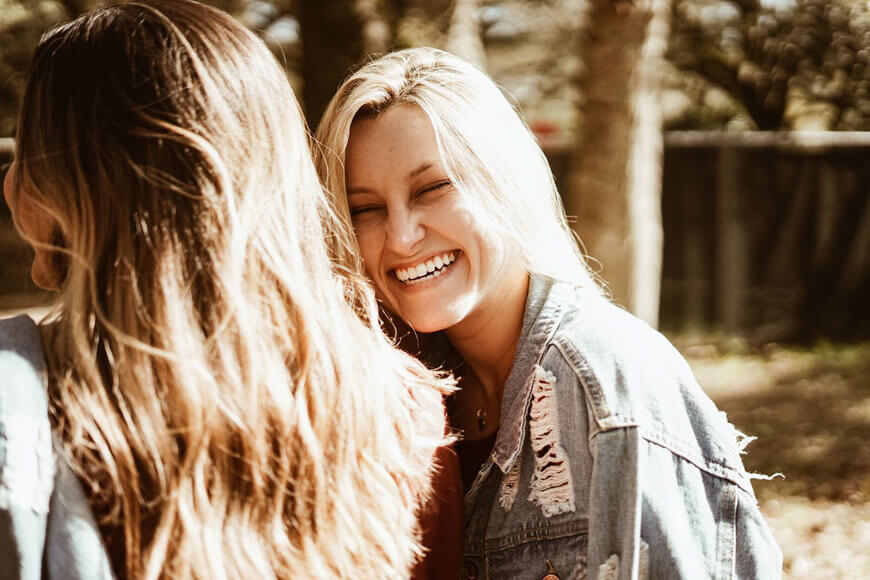 A woman laughs while chatting to a friend.