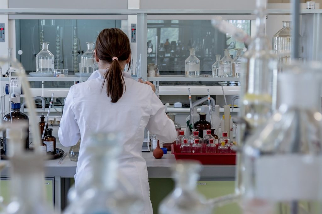 The back view of a researcher in a lab-coat next to a tray of bottles and a bulb syringe