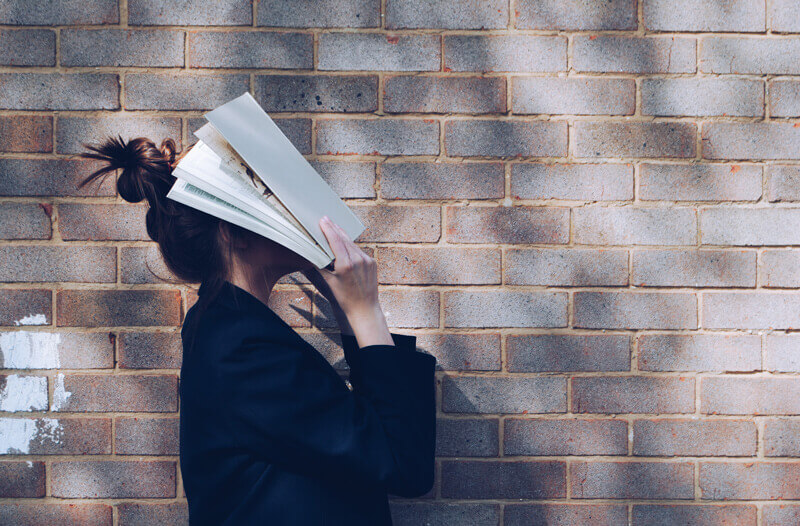 Woman-holds-books-to-her-face-in-frustration