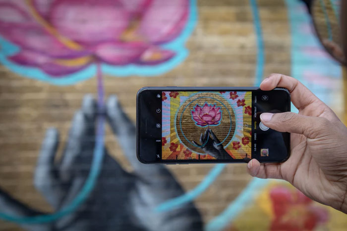 The view of someone taking an iPhone picture of a religious painting featuring a pink lotus.