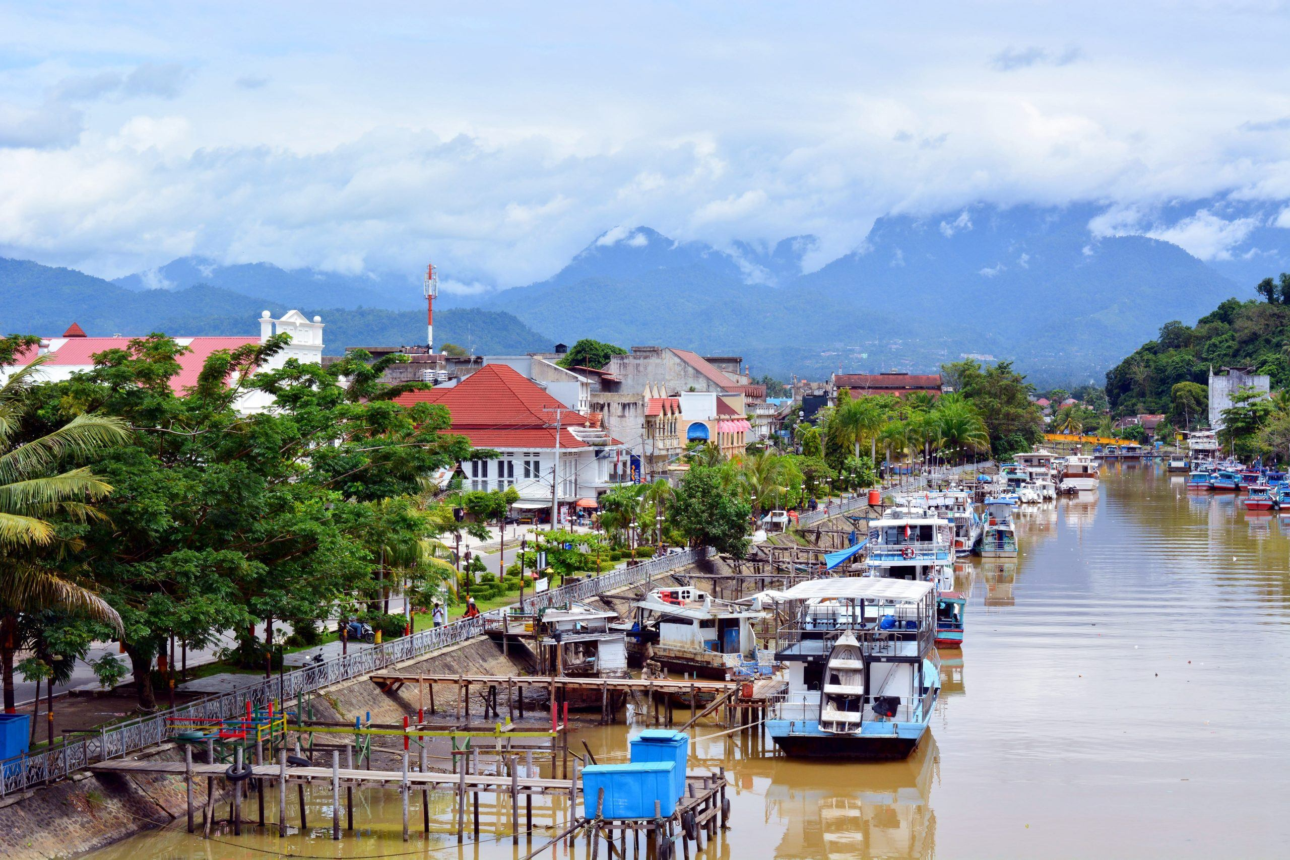 A view of a Sumatran riverside village against a background of cloudy