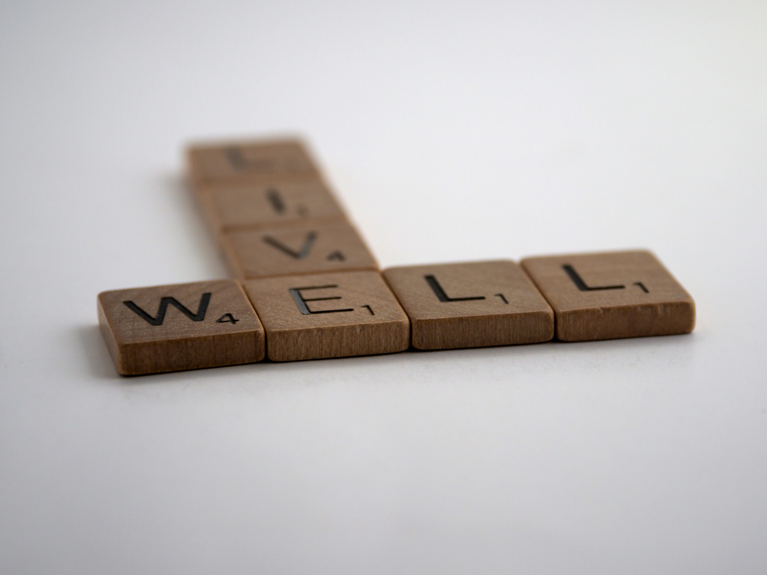 """Brown letter pieces spelling out """"Live Well"""" on a white background."""