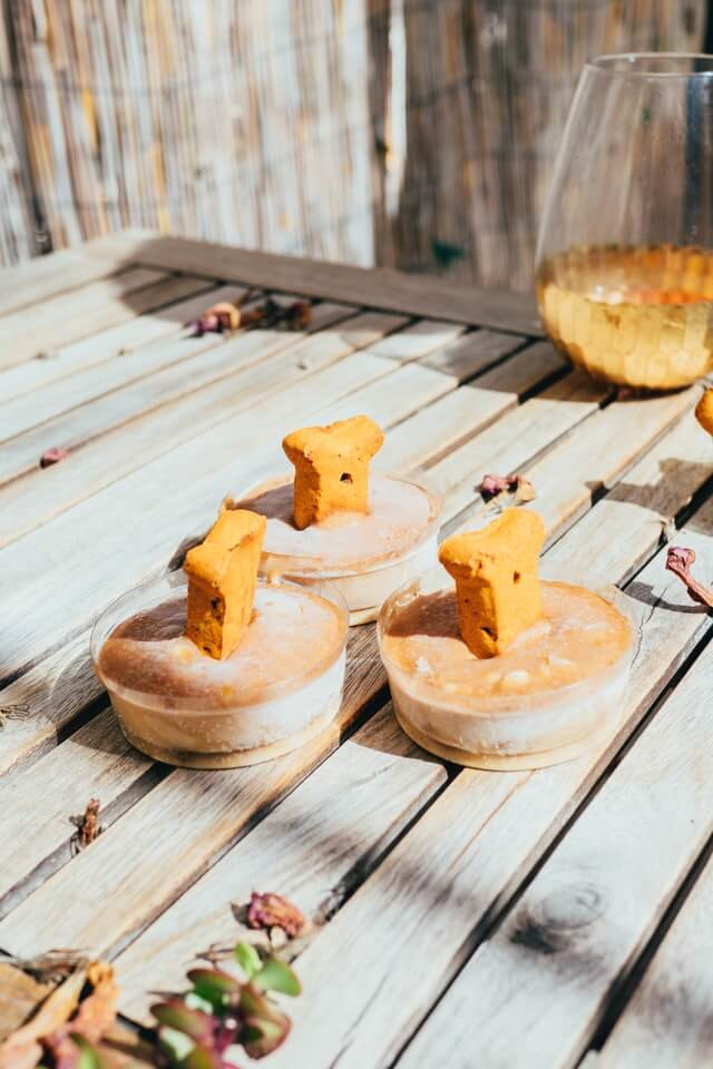 Three dog bowls with bones cooling off on a wooden table.