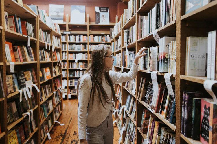 Woman browses bookshelves full of books